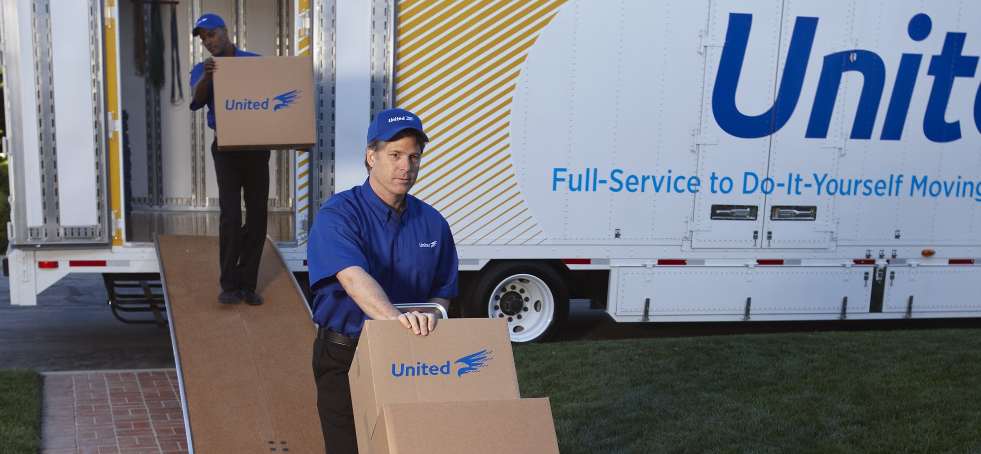 two men moving boxes off a United van